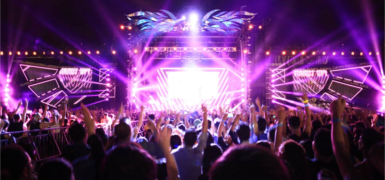 Crowds enjoying themselves at an Electronic Music Festival.