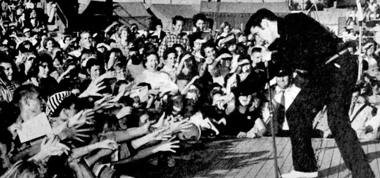 A black-and-white photograph of Elvis Presley on stage