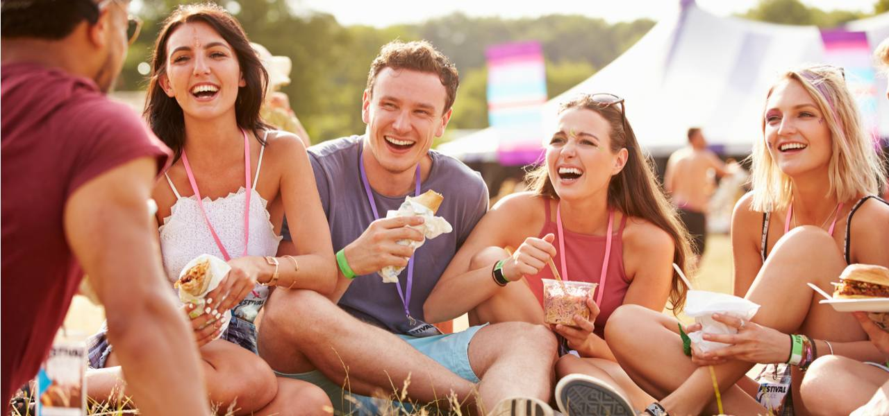 Friends eating and laughing at festival