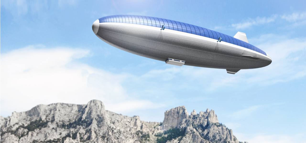 An artist's impression of a futuristic airship with a solar panel roof drifts over a mountain range