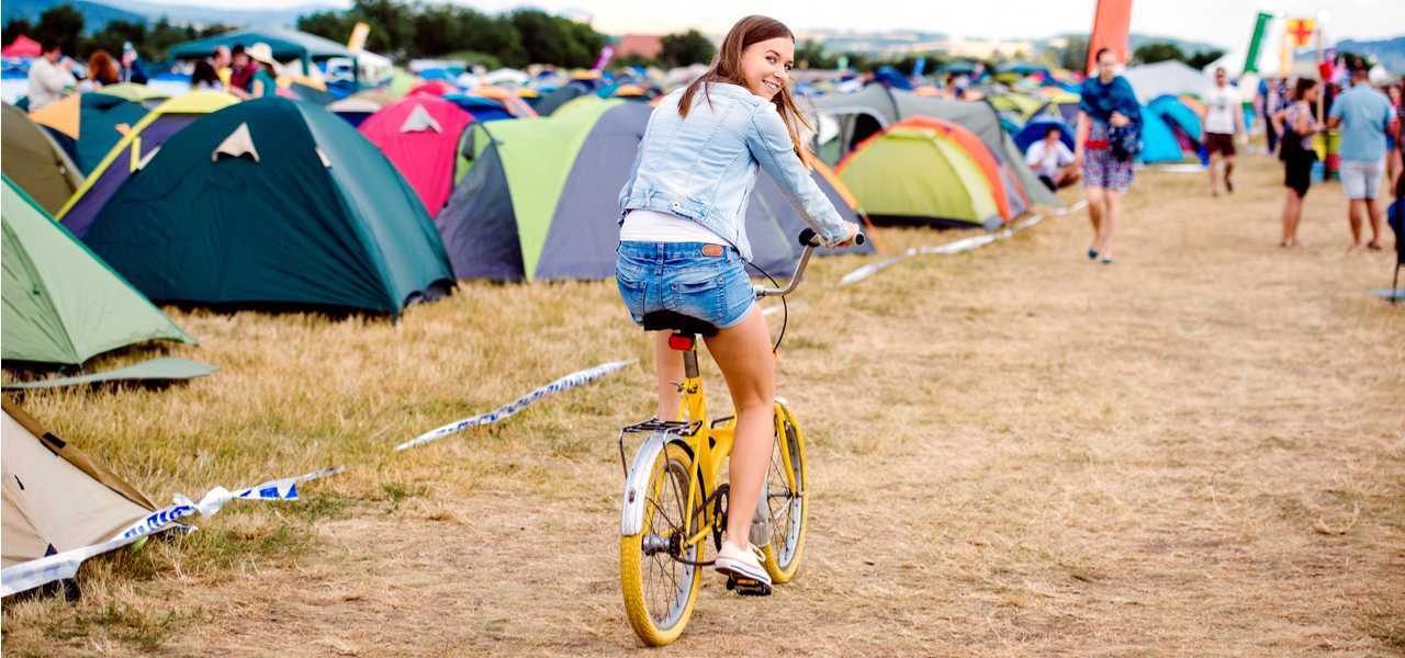 A girl rides a bicycle through the camp ground at a music festival