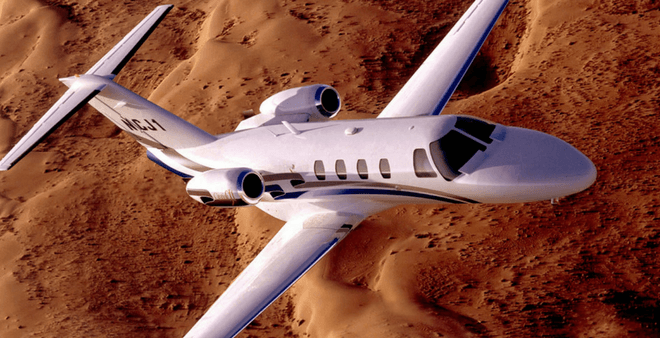 Cessna private jet flying over sand dunes