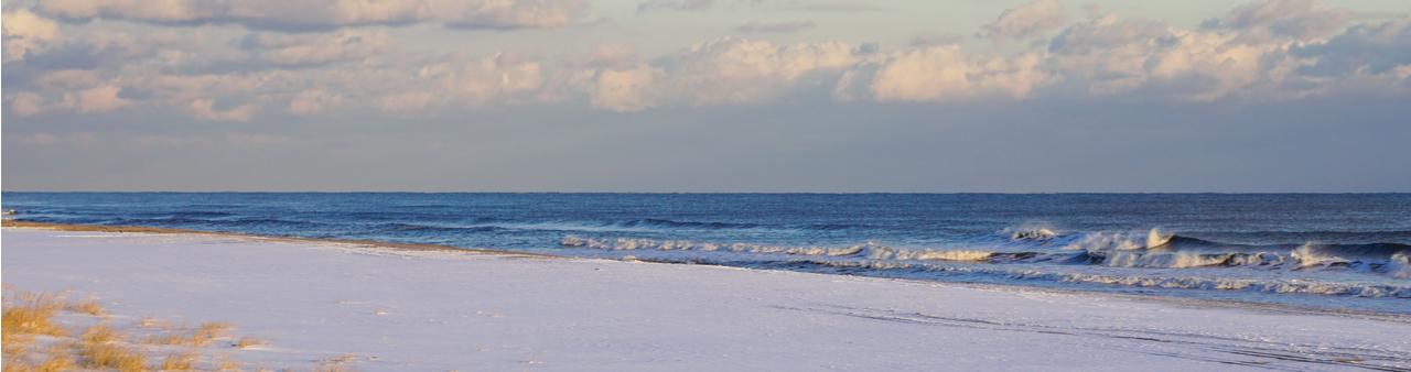 Atlantic ocean waves on the beach at the Hamptons, Long Island, in winter at dawn