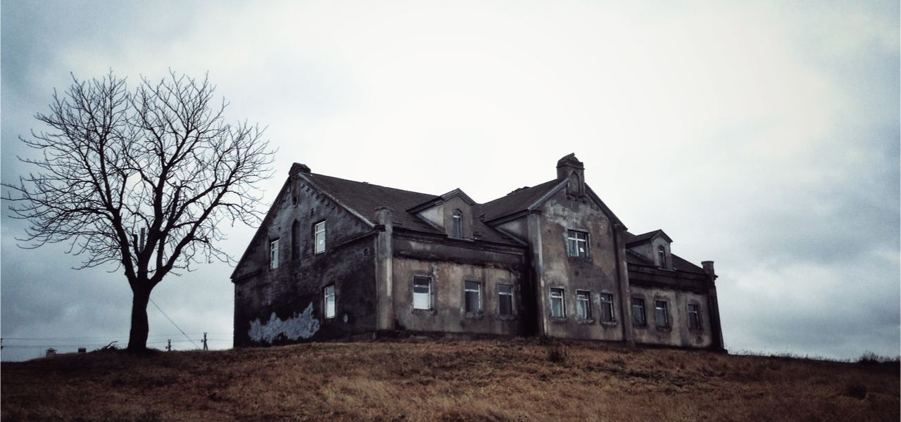 Photo of an old scary abandoned house that is deteriorating with time and neglect