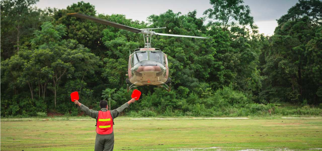 An air-traffic controller signals to a helicopter as it lands in a remote area