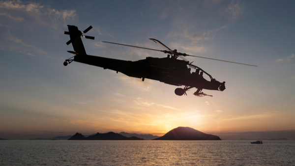 Helicopter flying over sea at sunset