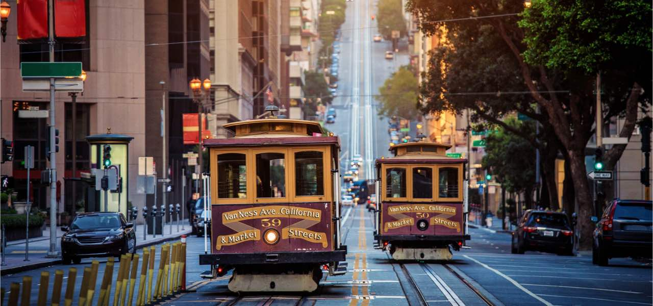 Historic Cable Cars riding on California Street in morning light at sunrise in San Francisco