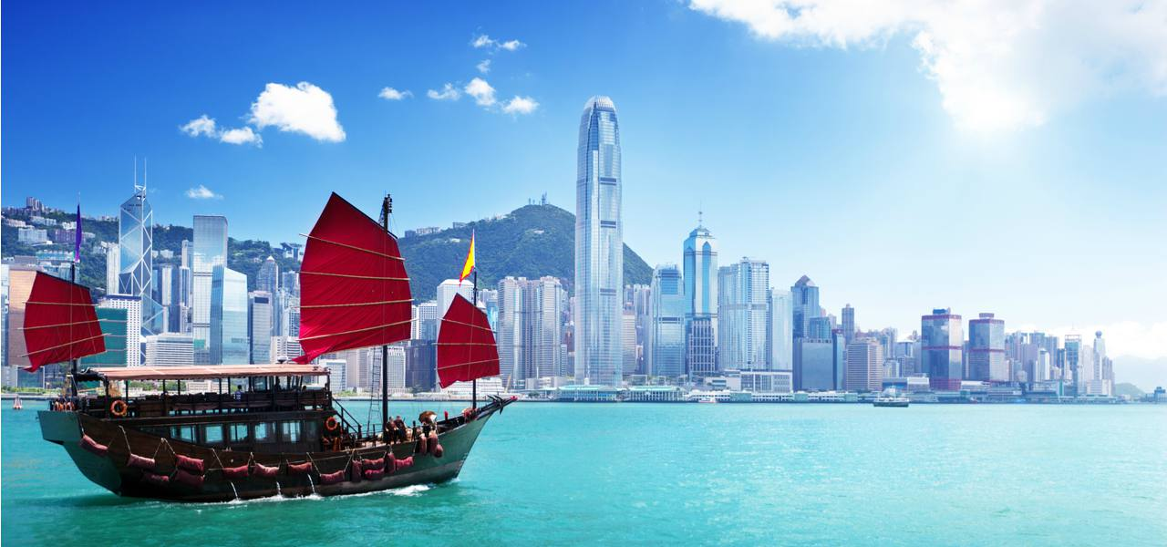 A traditional Chinese boat cruises past skyscrapers in off the coast of Hong Kong