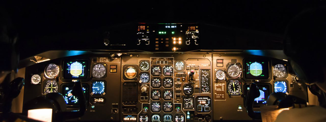 An illuminated cockpit panel display on a large commercial aircraft at night