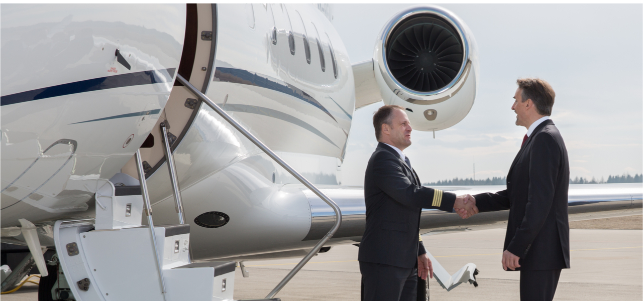 Businessman shakes hands with private jet pilot