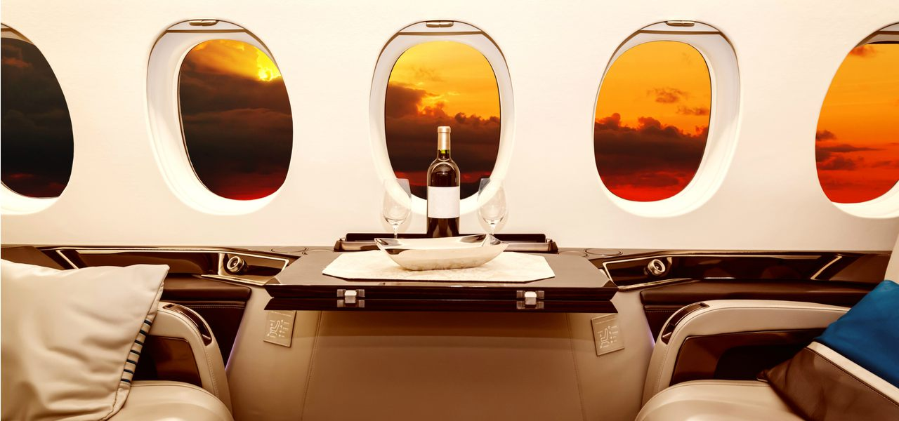 Interior of a luxury jet with an orange and red sunset out of the window
