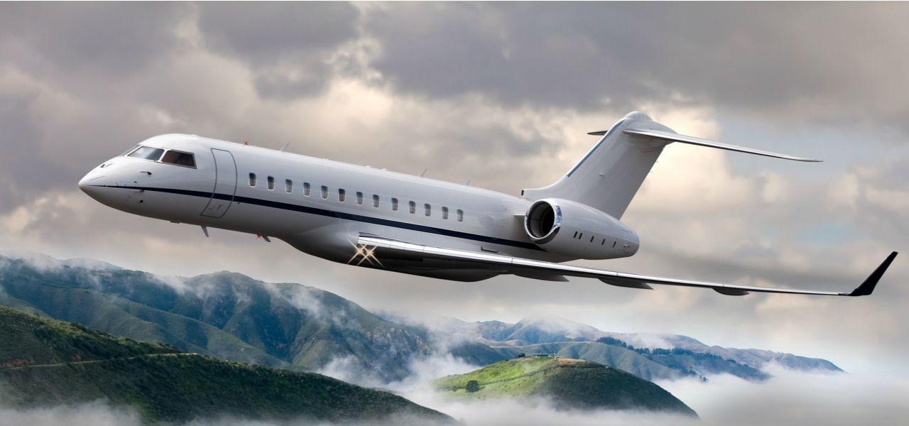 A private jet flies through clouds over a mountainous landscape