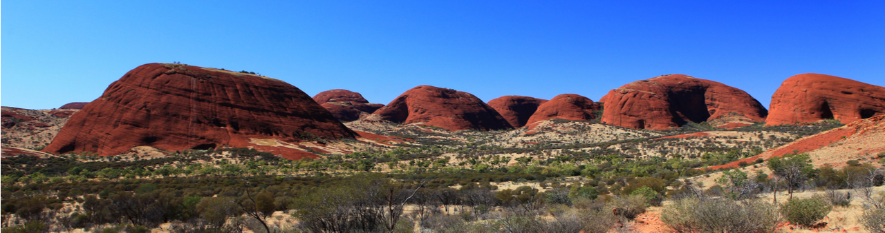 Red canyons and wild desert land, with a bright blue sky overhead, in Central Australia