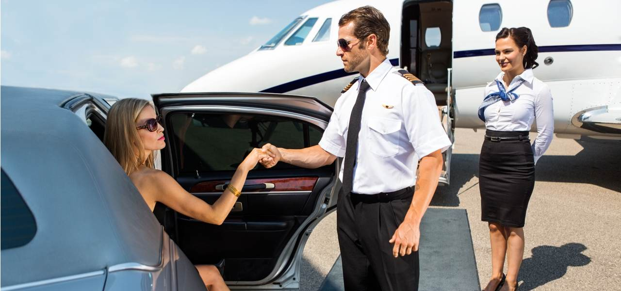 A woman is escorted from her car by a private jet pilot