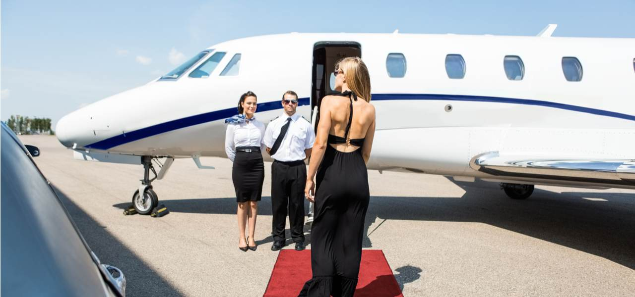 A lady in a black dress walks along a red carpet to board a private jet