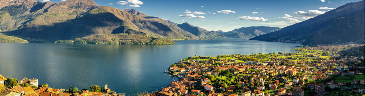 Lake Como at dawn, from above with a picturesque lakeside town below