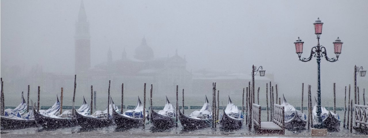 A line of gondolas in Venice under a dusting of snow at dawn