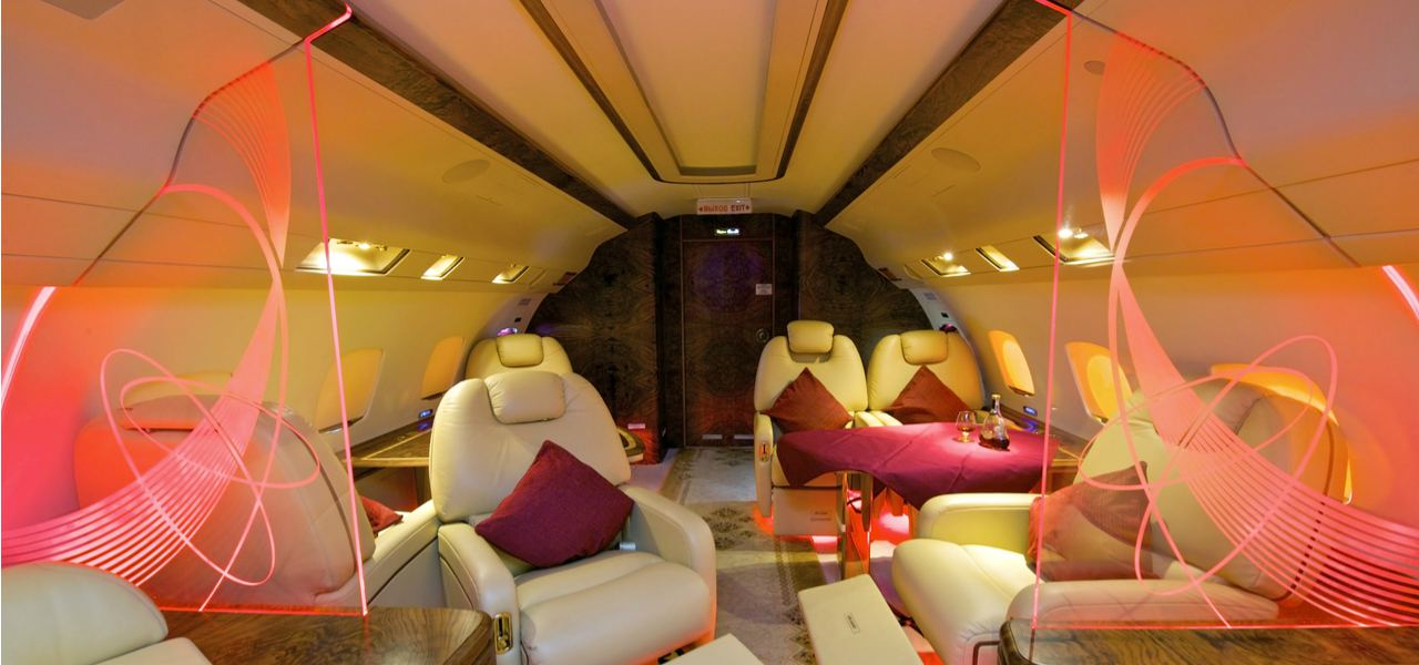 A lavish private plane interior with designer seating, lighting and dividers
