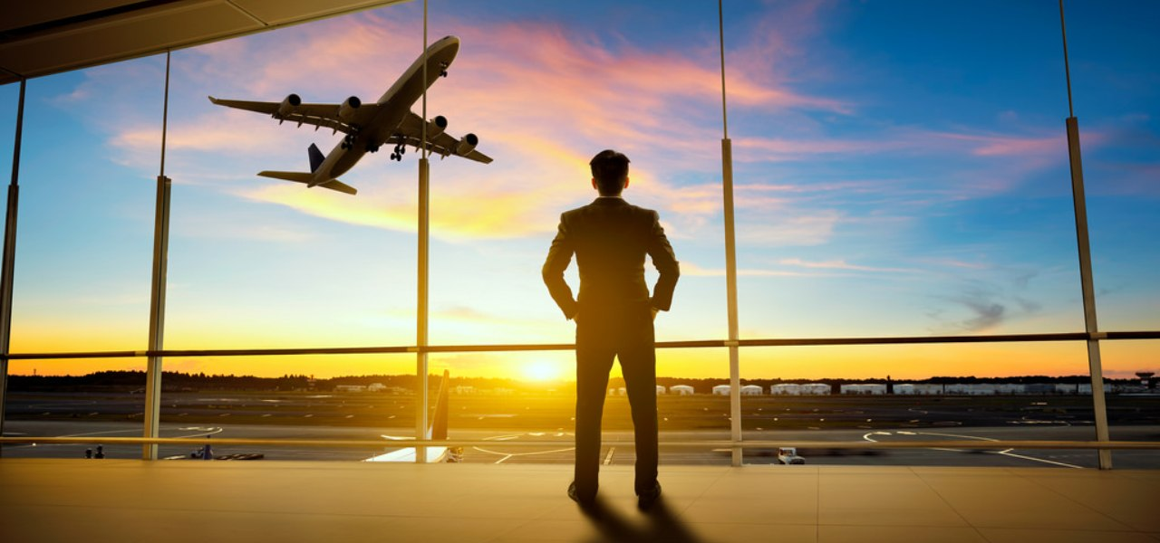 Business man in a suit at an airport watching a plane take off in to the sunset