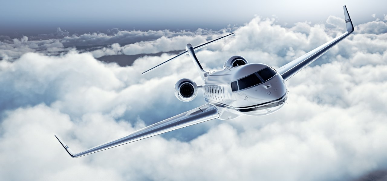 Modern private business jet flying over the clouds.