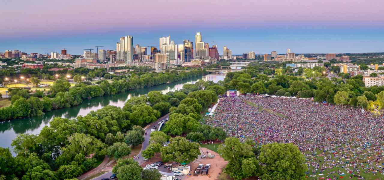 View over Zilker Metropolitan Park during Austin City Limits Music Festival with the city in the background.