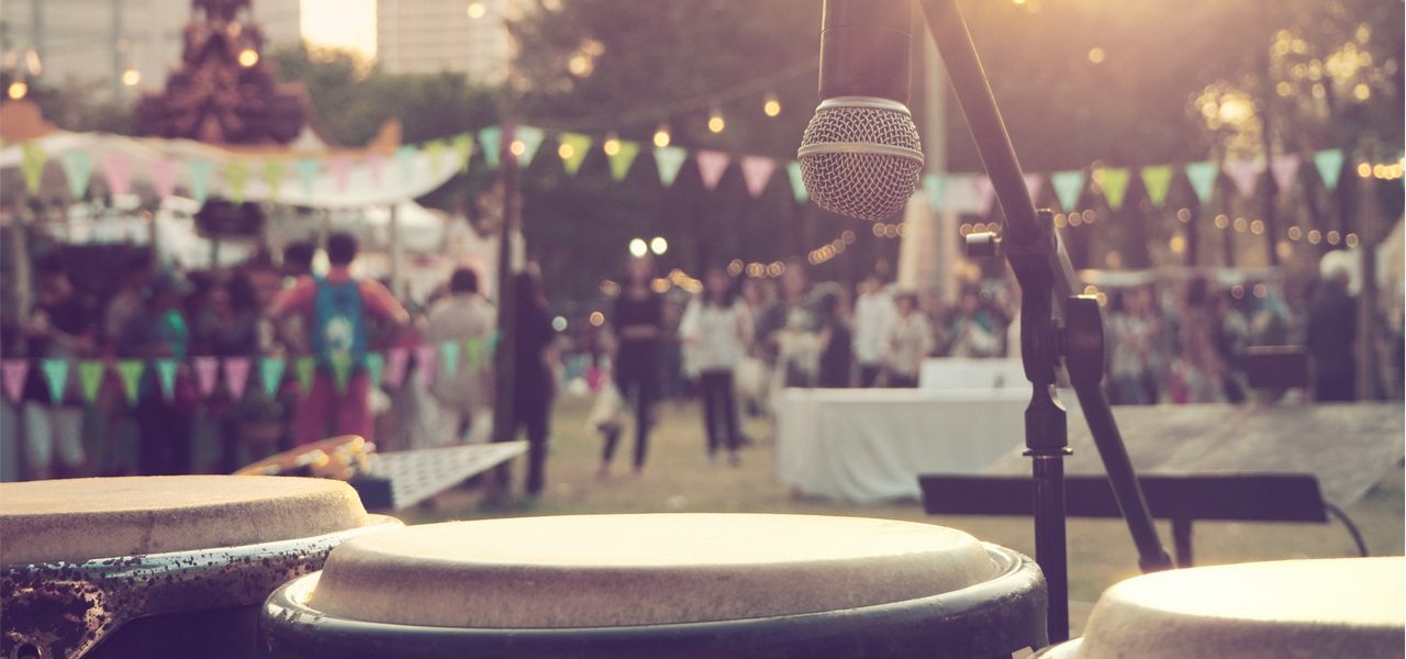 Photo taken from the stage of a music festival with the musical instruments in the foreground.