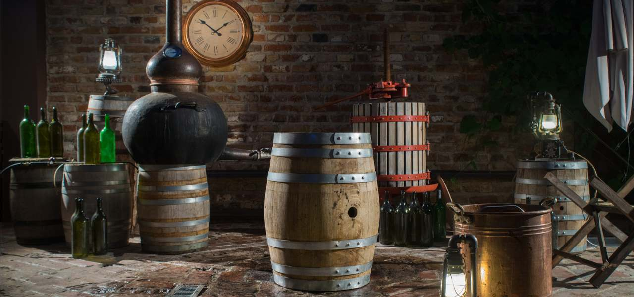 Oak barrels and a still inside a small distillery