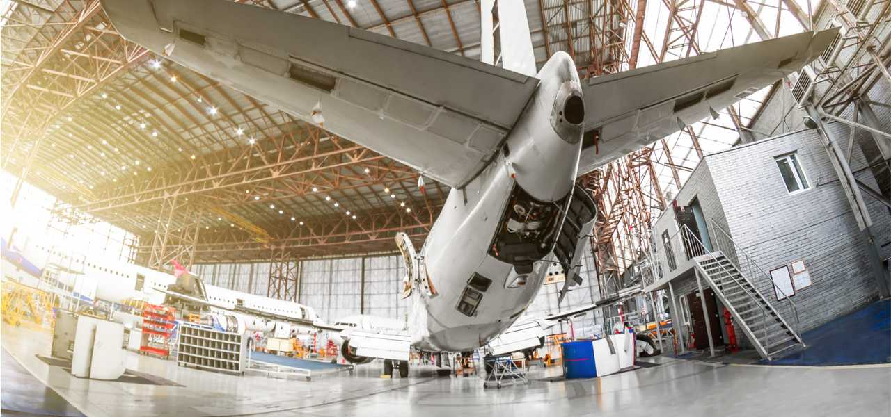 Maintenance of a passenger aircraft in an aviation hangar, rear-view of the tail, on the auxiliary power unit.