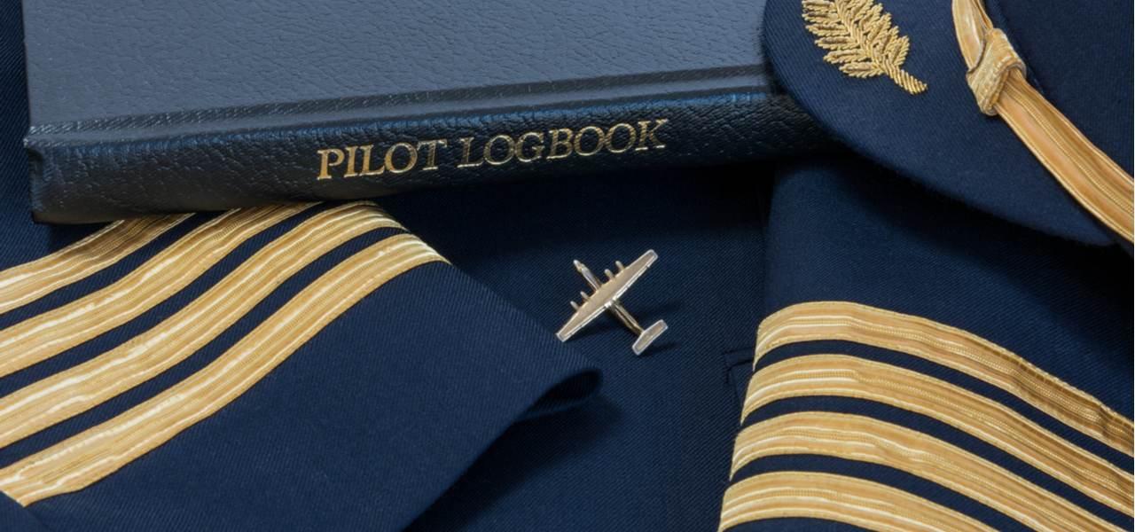 A pilot's logbook, badge and cap
