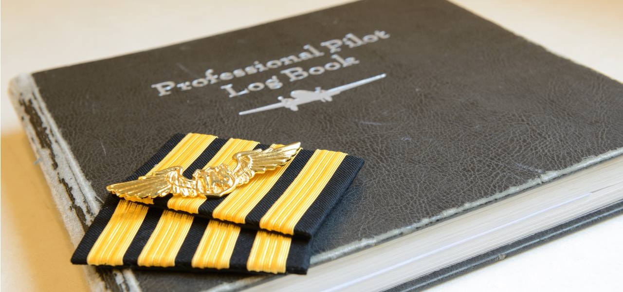 A pilot's logbook and badge