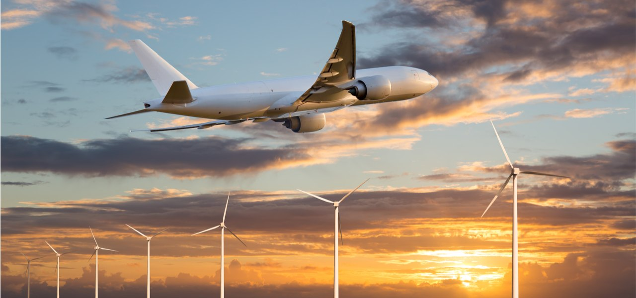 Passenger plane taking off at sunset above wind electric generators.
