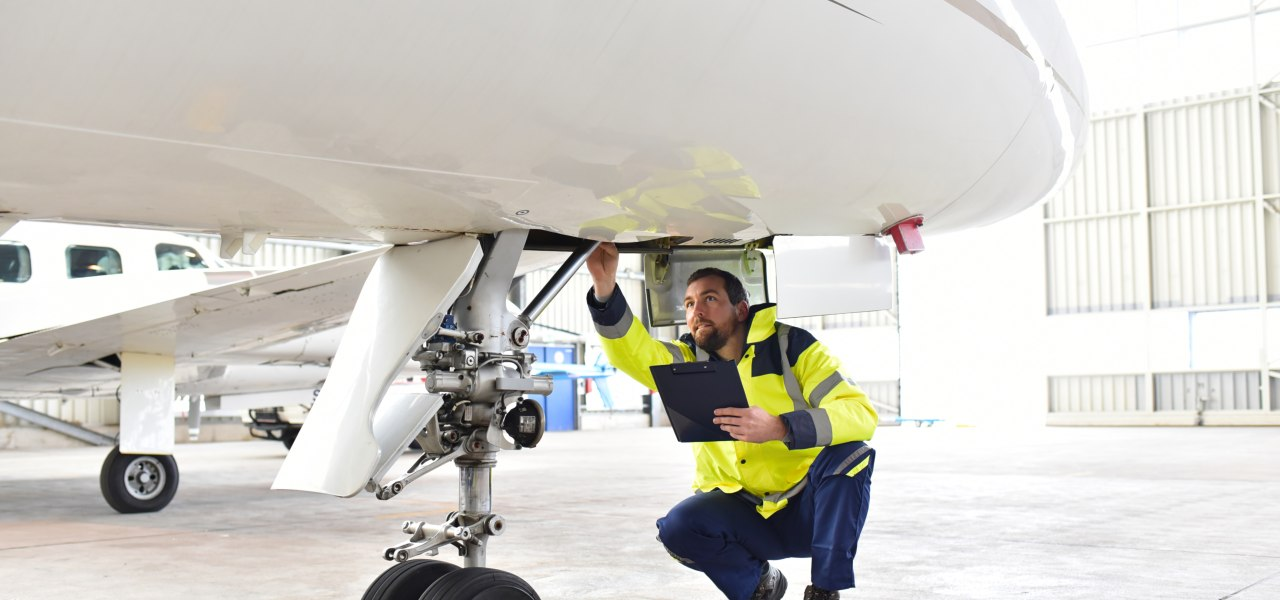 Official ground personnel leading a pre-buy inspection and checking the hydraulic system of the landing gear of the aircraft