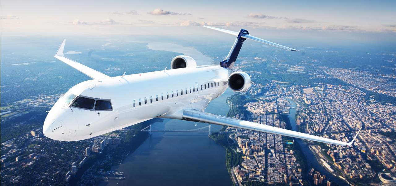 Private jet flying over a city