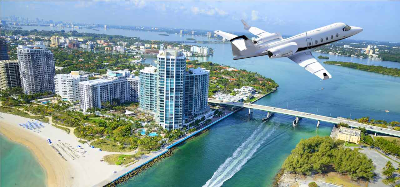 Private jet flying over Miami Beach