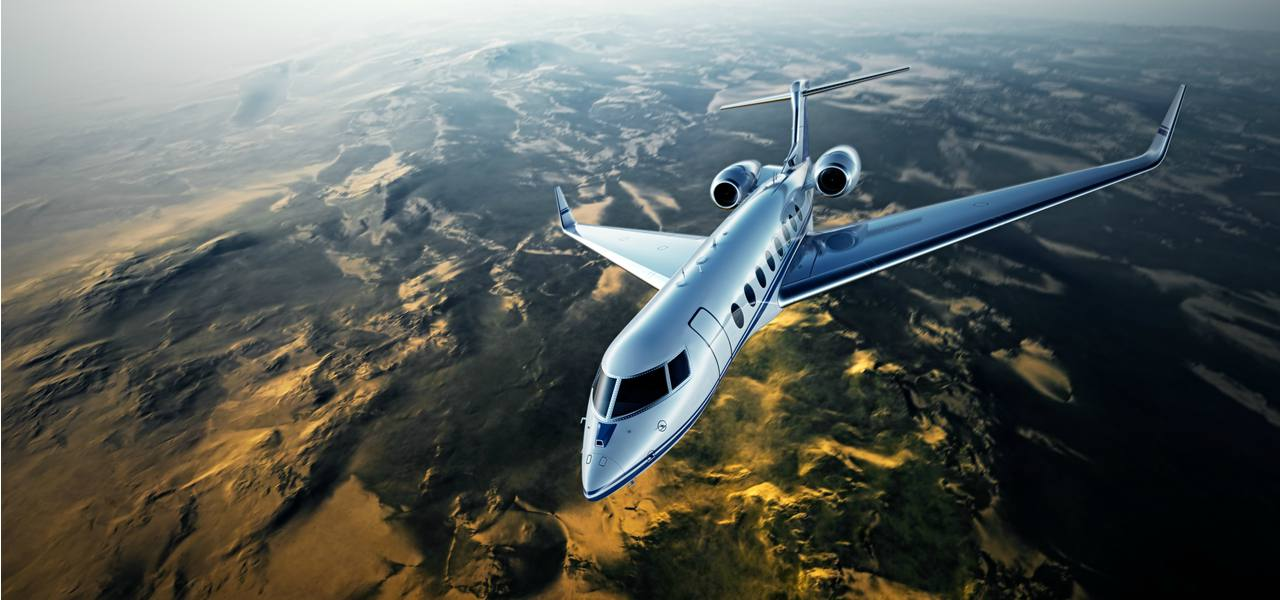A private jet flying over mountains