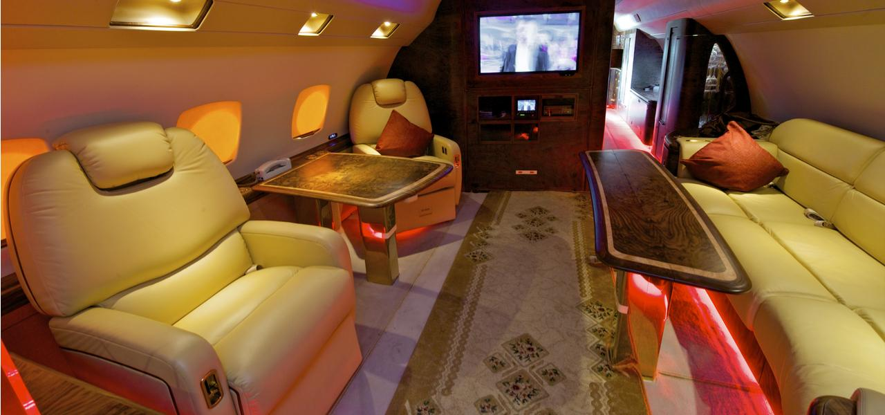 The interior of a private jet, featuring leather couches, a decorative carpet and a wood-finish in-flight entertainment unit