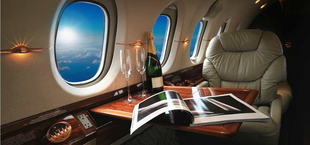 Private jet interior with champagne bottle and two glasses