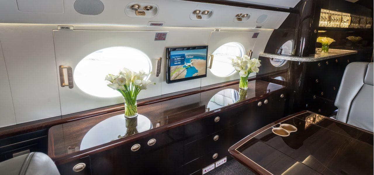 Интерьер частного самолета с двумя вазами белых цветов