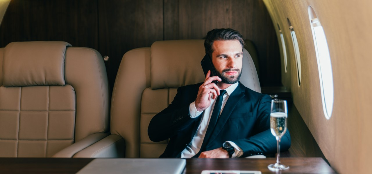 Man in a suit talking on a mobile phone looking out of the window of a private jet, with a glass of champagne in the foreground