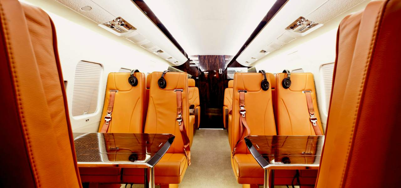 Private plane interior with wooden tables and brown leather seats