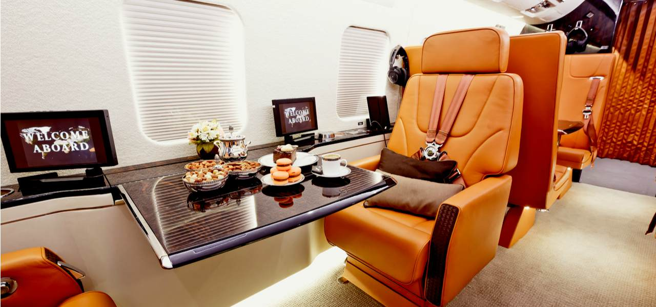 Private plane interior with wooden tables with food and leather seats