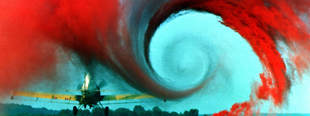 A propellor airplane leaves a turbulent vortex, highlighted by red smoke