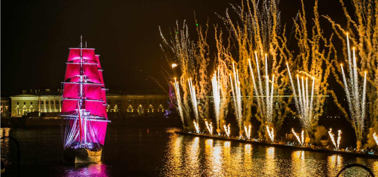 A ship with scarlet sails floats down the Neva river against a background of fireworks