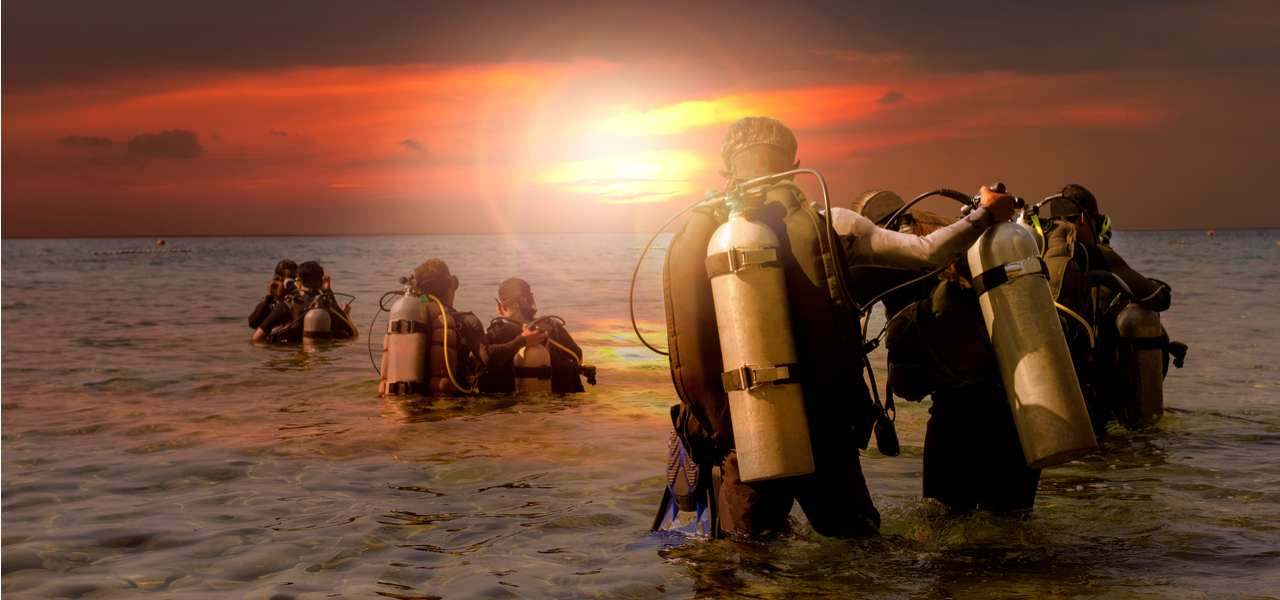 A group of SCUBA divers prepares to enter the water at sunset