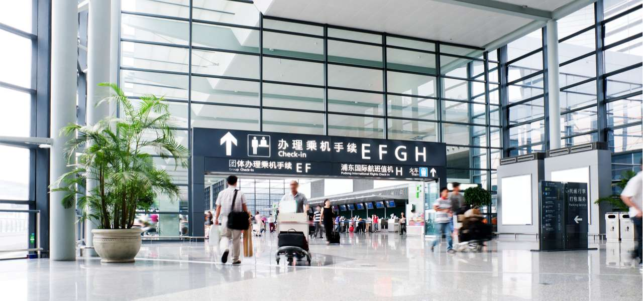 Interior view of the Shanghai Pudong airport, with passengers walking during the day.
