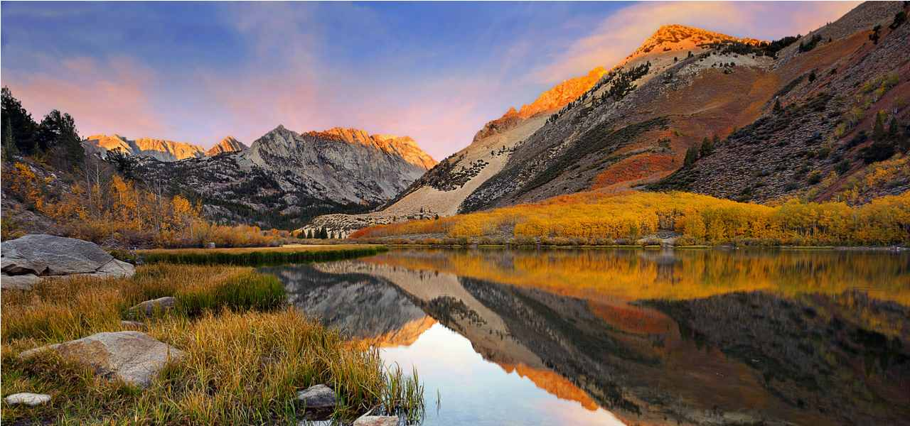 A small lake in the Sierra Nevada reflecting the scenery at dawn