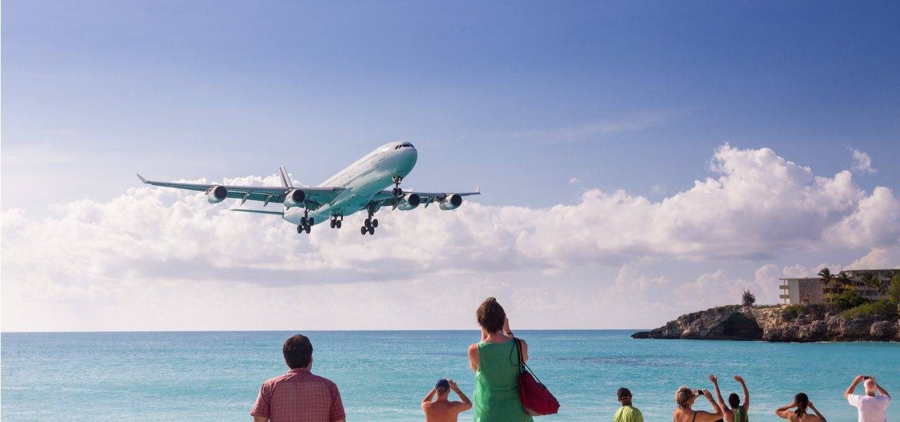 An airliner lands over beach-goers outside Sint Maarten Princess Juliana Airport
