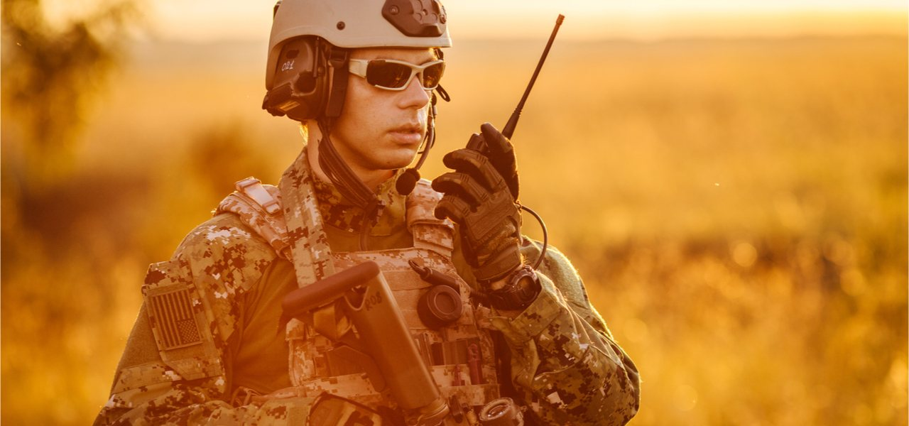 Portrait of young nato soldier holding a radio station