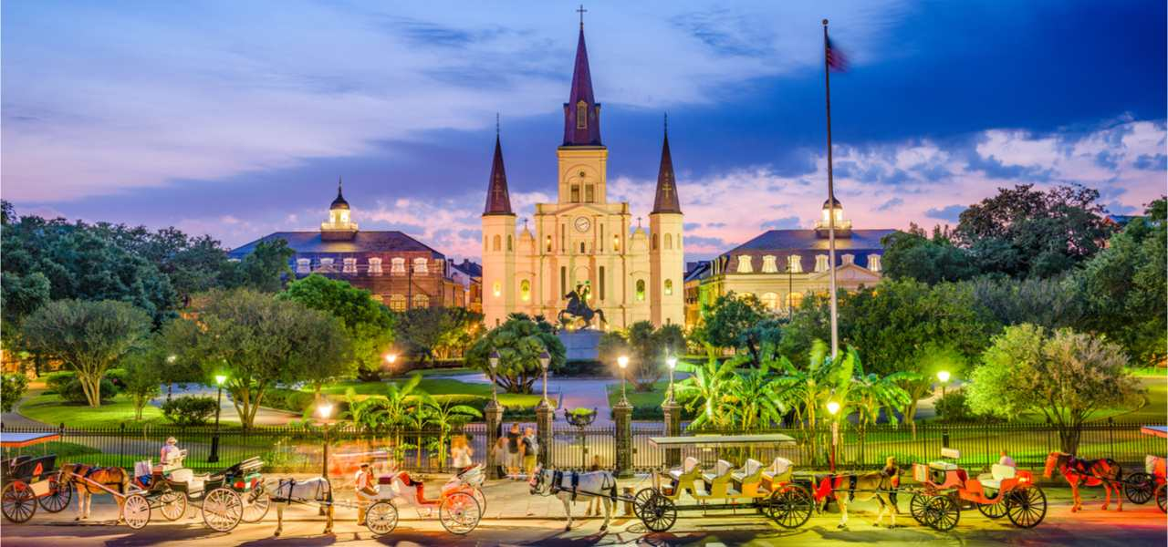 A photo of horse-drawn carriages at sunset in New Orleans with St. Louis Cathedral and Jackson Square in the background.