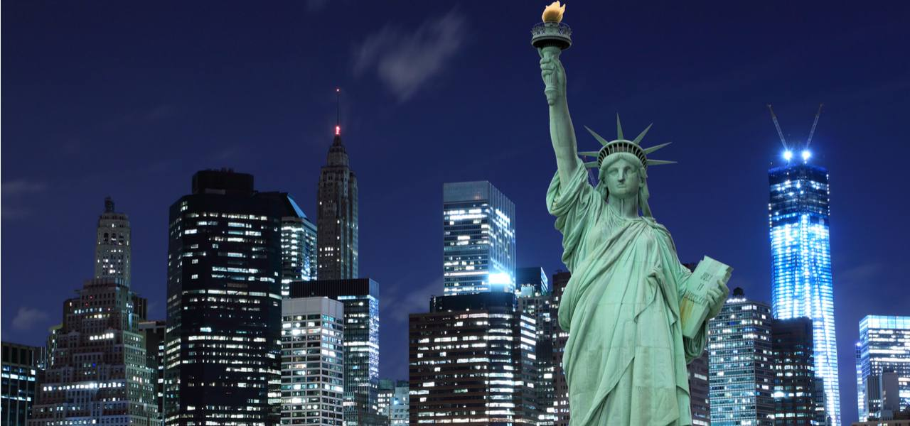 Statue of Liberty in front of Manhattan skyline at night